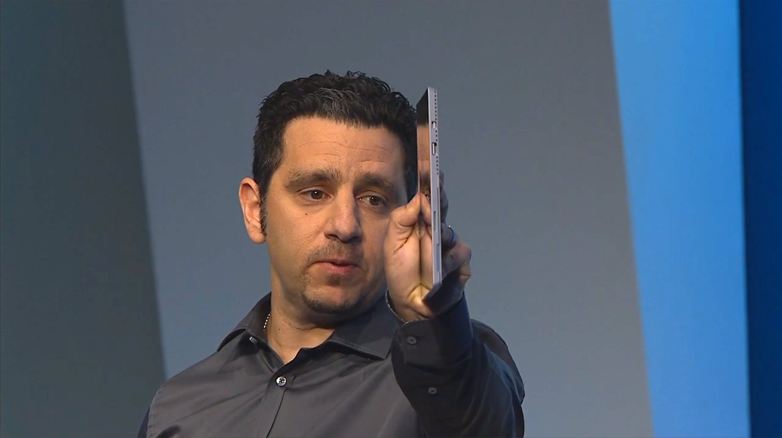 Panos Panay holds the device edge-on for the audience to see how thin it is.
