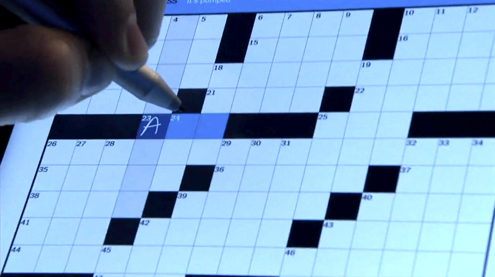 Panos Panay writes the letter 'A' into a box on a crossword.
